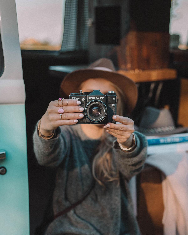 Dlaczego warto obrabiać zdjęcia w Lightroomie? Zdjęcie przedstawia dziewczynę, trzymającą przed sobą aparat fotografuczny w klimacie vintage.